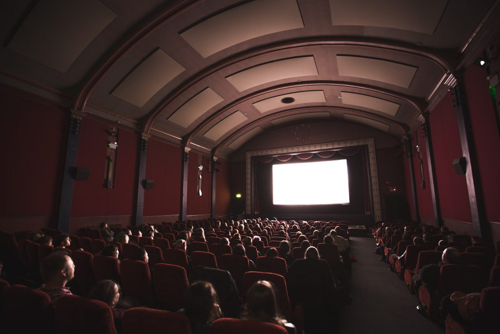 A moderately crowded movie theater is shining a bright white light from a movie screen onto the seated audience.